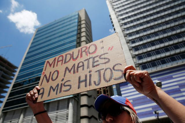 An opposition supporter holds a placard during a rally to commemorate International Women's Day and in support of jailed opposition leaders, Leopoldo Lopez and Antonio Ledezma, in Caracas