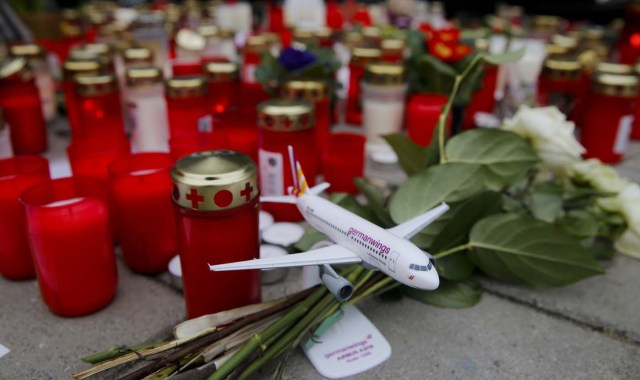 Flowers and lit candles are placed on the ground in Cologne Bonn airport