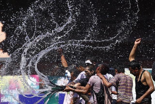 Varios nepaleses rocían agua y bailan mientras participan en las celebraciones por el Festival Holi en Katmandú (Nepal) hoy, jueves 5 de marzo de 2015. El Holi, of Festival de los Colores, anuncia el inicio de la primavera y se celebra en Nepal e India durante días. EFE/Narendra Shrestha