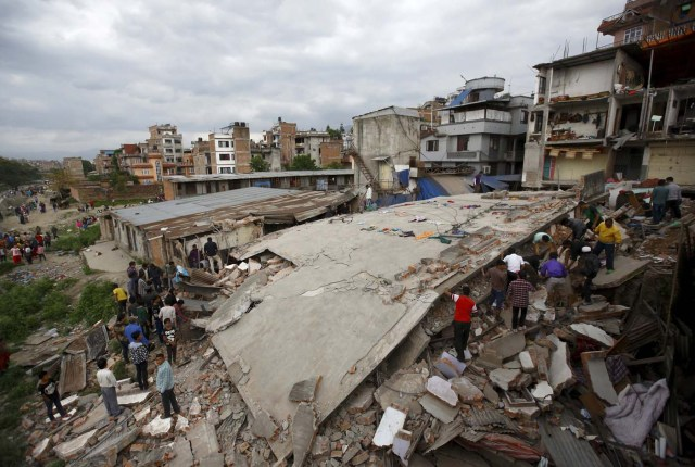 People gather near a collapsed house after major earthquake in Kathmandu