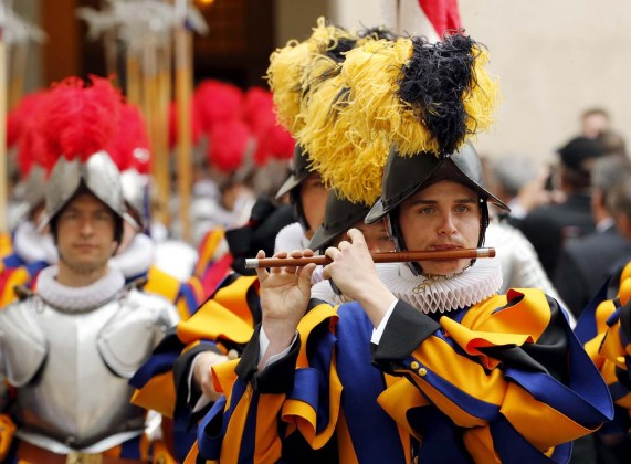 A new recruit of the Vatican's elite Swiss Guard plays an instrument as they march during the swearing-in ceremony at the Vatican