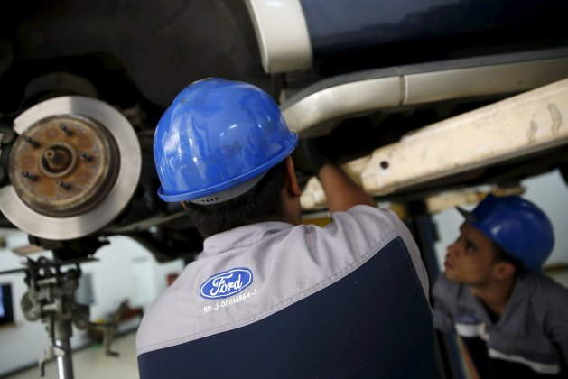 The corporate logo of Ford is seen on the uniform of a mechanic at a Ford branch in Caracas