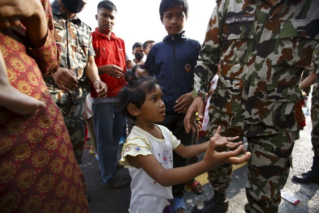 Girl spreading her arms asks soldiers for food near a makeshift shelter after the April 25 earthquake in Kathmandu