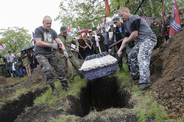 Varios rebeldes prorrusos entierran el ataúd con los restos mortales de Alexéi Mozgovói, jefe de una brigada de milicianos prorrusos, durante su funeral en Alchevsk, en la región de Lugansk, Ucrania, hoy, miércoles 27 de mayo de 2015. Mozgovói, de 40 años, murió el pasado 23 de mayo en una carretera de la región de Lugansk, cuando el microbús en que viajaba fue alcanzado por la explosión de una mina y luego ametrallado por un grupo. EFE/Alexander Ermochenko