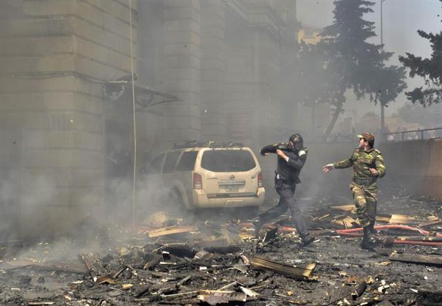 Dos policías corren escapando de los escombros que caen de un edificio de pisos incendiado en Bakú, Azerbaiyán, hoy, martes 19 de mayo de 2015. Al menos quince personas murieron hoy y 30 tuvieron que ser hospitalizadas a consecuencia de un incendio en un edificio de 16 plantas situado en el barrio de Binagadi, en el norte de la capital azerbaiyana, que los bomberos han tardado varias horas en sofocar. El fiscal general, Zakir Garálov, adelantó como posible causa del siniestro la mala calidad del revestimiento aislante del edificio, que fue donde se originó el fuego, según testigos. EFE/Orxan Azim