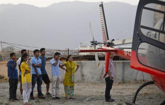 """Los familiares de las víctimas de un helicóptero accidentado lamentan la tragedia, mientras los cuerpos son trasladados al hospital universitario de Katmandú, Nepal, hoy, martes 2 de junio de 2015. Cuatro personas murieron hoy cuando el helicóptero en el que viajaban se estrelló mientras distribuía ayuda en el distrito de Sindhupalchwok, una de las áreas más afectadas por el terremoto que golpeó hace seis semanas Nepal. """"Hemos visto cuatro cadáveres hasta ahora"""", dijo el Ejército en un comunicado, en el que indicó que entre los fallecidos se encuentran tres hombres, entre ellos el capitán de la aeronave, y una mujer. EFE/Narendra Shrestha"""
