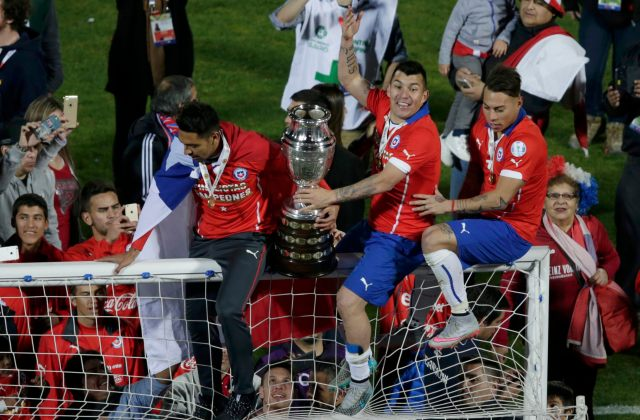 Chile players Vargas and Medel climb atop the goal with the Copa America trophy as they celebrate their team's victory over Argentina in their Copa America 2015 final soccer match at the National Stadium in Santiago
