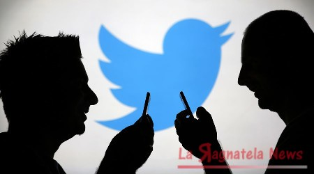 Men are silhouetted against a video screen with a Twitter logo as he poses with a Samsung S4 smartphone in this photo illustration taken in the central Bosnian town of Zenica, August 14, 2013. REUTERS/Dado Ruvic (BOSNIA AND HERZEGOVINA - Tags: BUSINESS TELECOMS) - RTX12L6S