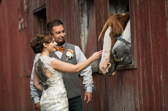 bride and groom pet horses in barn at Bunnell Farm