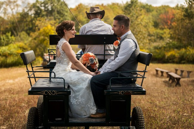 Bride and groom head to barn reception in horse and carriage