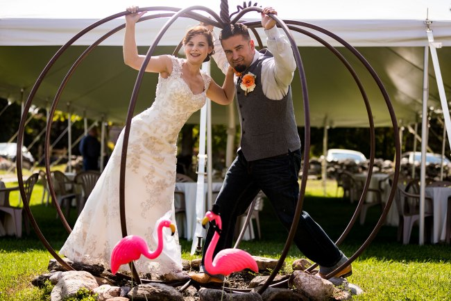 Bride and groom in giant pumpkin with pink flamingos