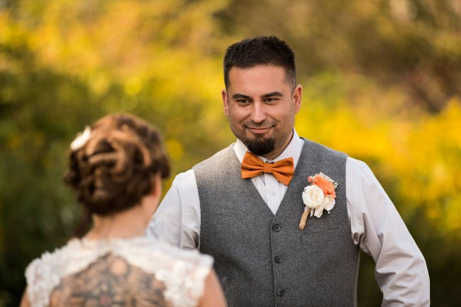 groom listens to the bride's wedding vows in a field in Litchfield