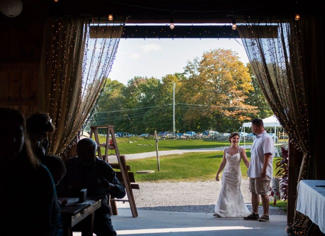 bride and groom make their grand entrance for their barn wedding reception