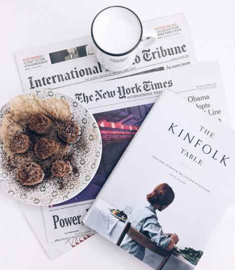 the kinfolk table book beside baked pastry on white ceramic plate with white ceramic mug
