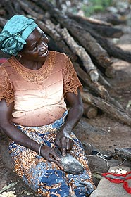 M'Batinin, who lives in the village of Koaba, has mastered six scarification patterns, but artists living close to the Togolese border know eight or more. M'Batinin is famous in Bétamarribé country for her excellent symmetry and speed with which she cuts human skin. Here she is sharpening her cutting tool; the cowrie shells she uses for divining sit by her knee.