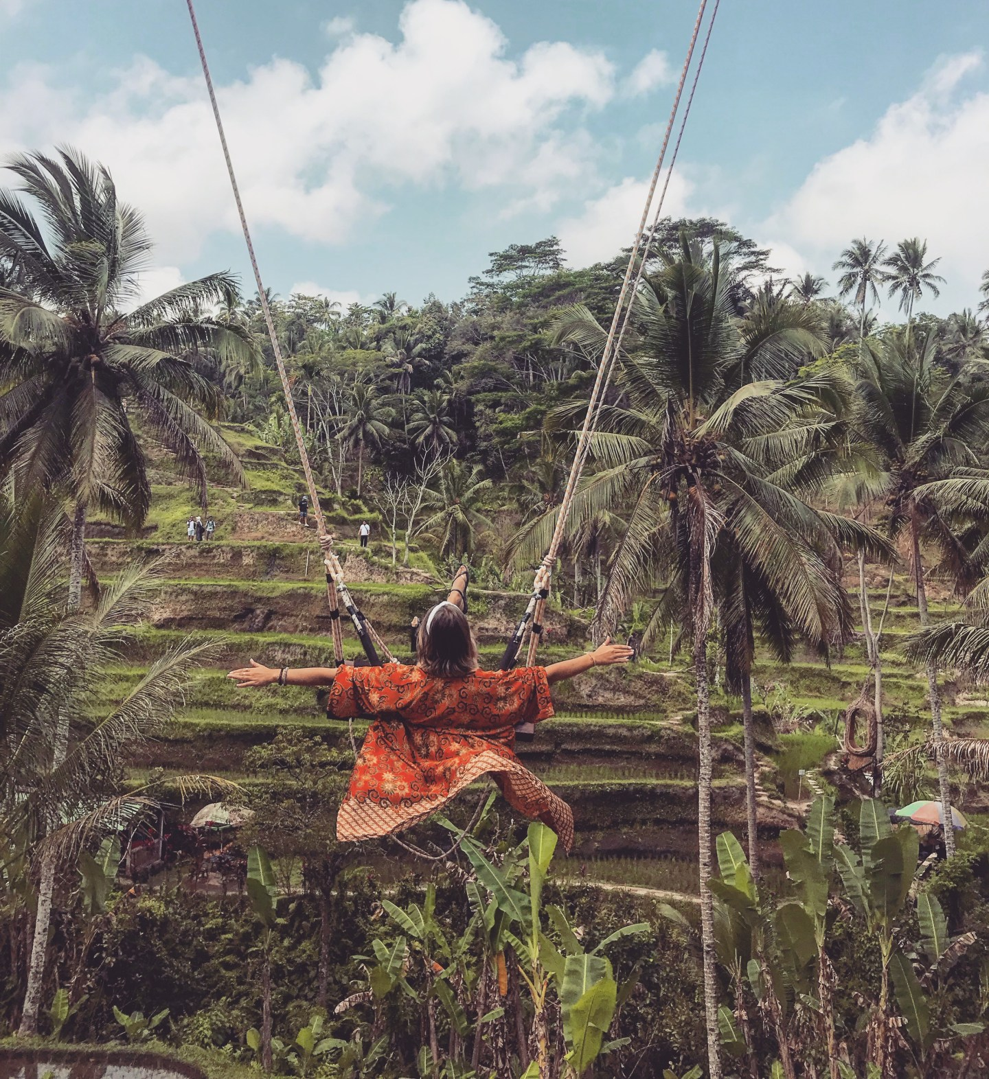 Sara Erb wears an orange kimono in the rice terraces of Tegallalang on Bali island in Indonesia, swinging on the Bali swing above the jungle.