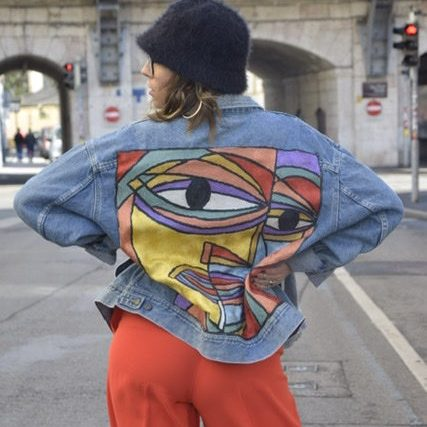 Blogger Sara Erb with denim jacket with embroidery detail from picasso painting from the back.