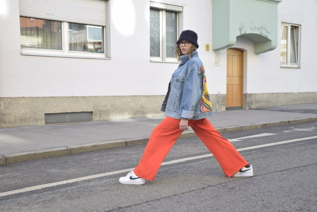 A cool stretchy pose for the artsy 90s style shooting in Innsbruck with red flare trousers, denim jacket and white sneakers of course.
