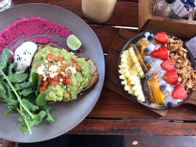 Foto vom Brunchessen im Bukit Café auf Bali. Avocado toast mit Chili, poached egg und dazu rote rübe hummus und rucola. als Nachspeise ein smoothie bowl mit frischen früchten und vielen nüssen.
