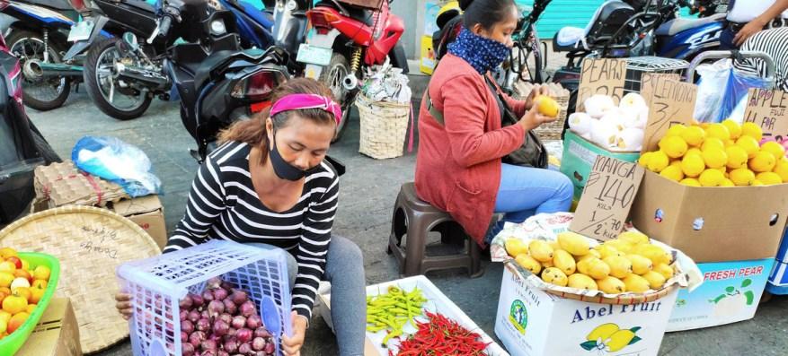 Las mujeres venden frutas y verduras en una acera en Filipinas, donde los trabajadores de la economía informal corren peligro de que sus medios de vida sean destruidos por los impactos del COVID-19.