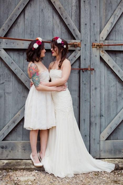 Couple de mariées devant une porte de grange