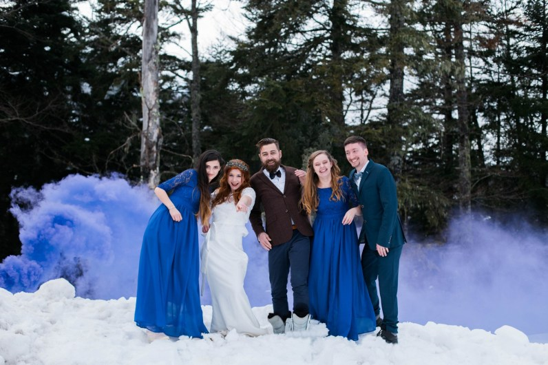 Mariés et leurs témoins dans la neige avec des fumigènes bleu