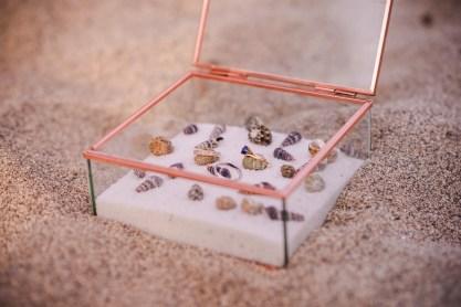 Boîte à alliances avec du sable et des coquillages