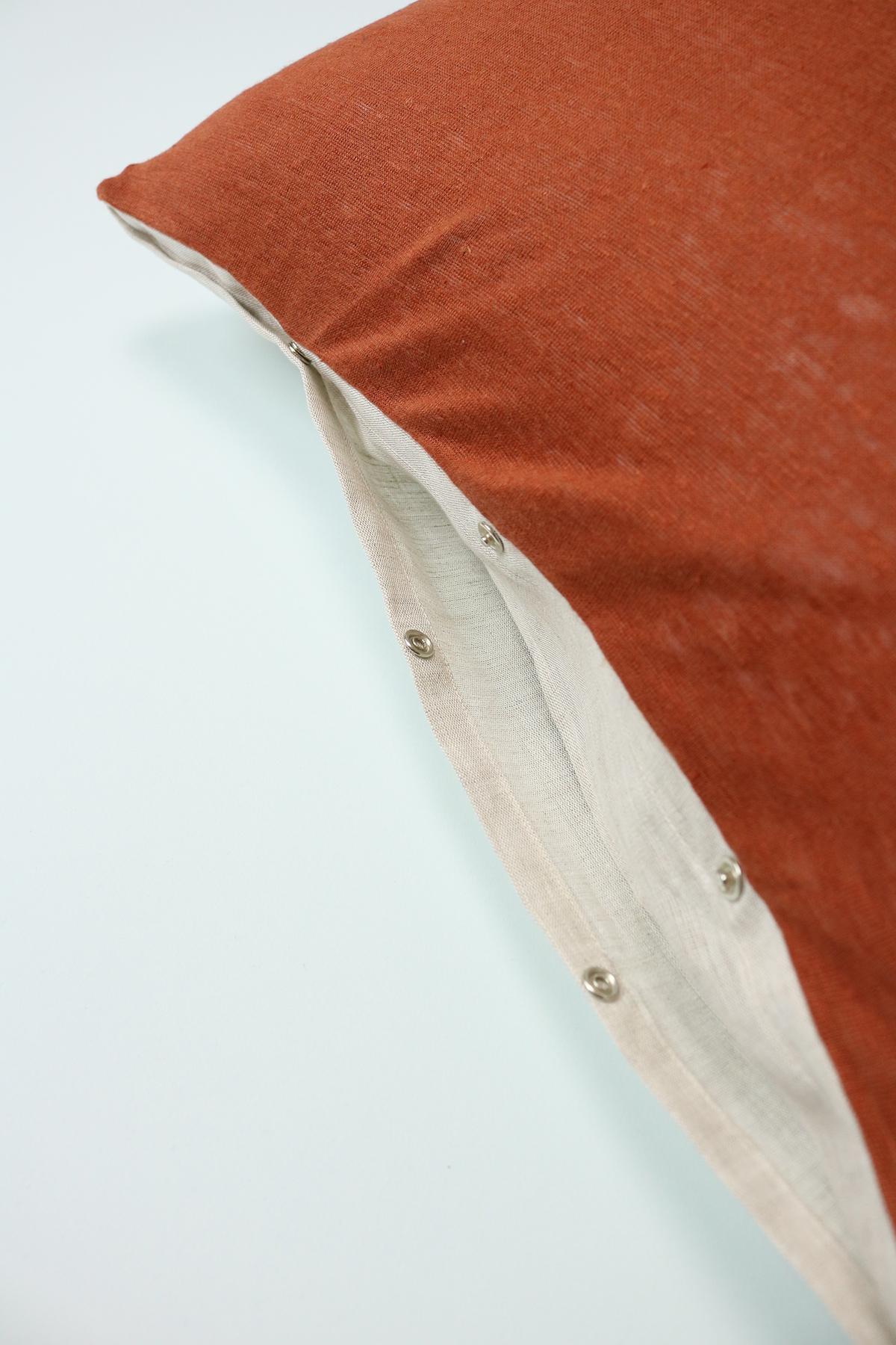 détail de l'ouverture par pressions de la housse de coussin Bowy, en jersey de lin roux avec un noeud en maille et lin chambray beige.