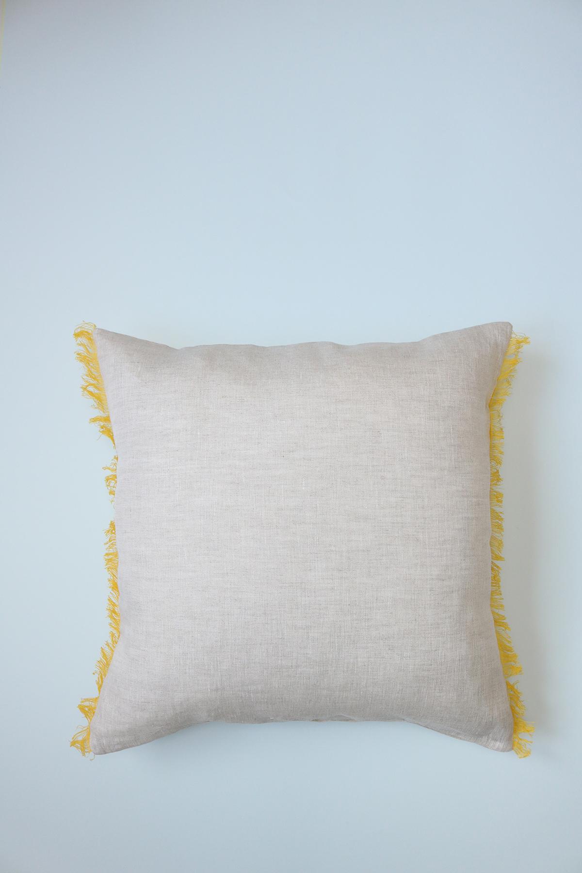 Voici la housse de coussin en lin Carmen, beige à franges jaunes sur les côtés.