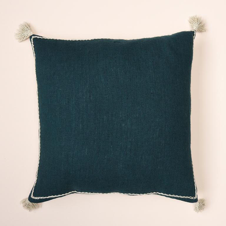 Voici la housse de coussin en lin lavé Jude, de couleur bleu de Prusse et beige brodé au fil beige et quatre pompons.