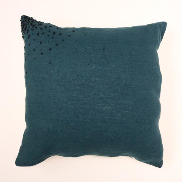 Voici la housse de coussin Prue. Réalisée en lin lavée bleu de Prusse et lin beige chambray sur l'arrière, elle est brodée d'un fil noir sur un angle.