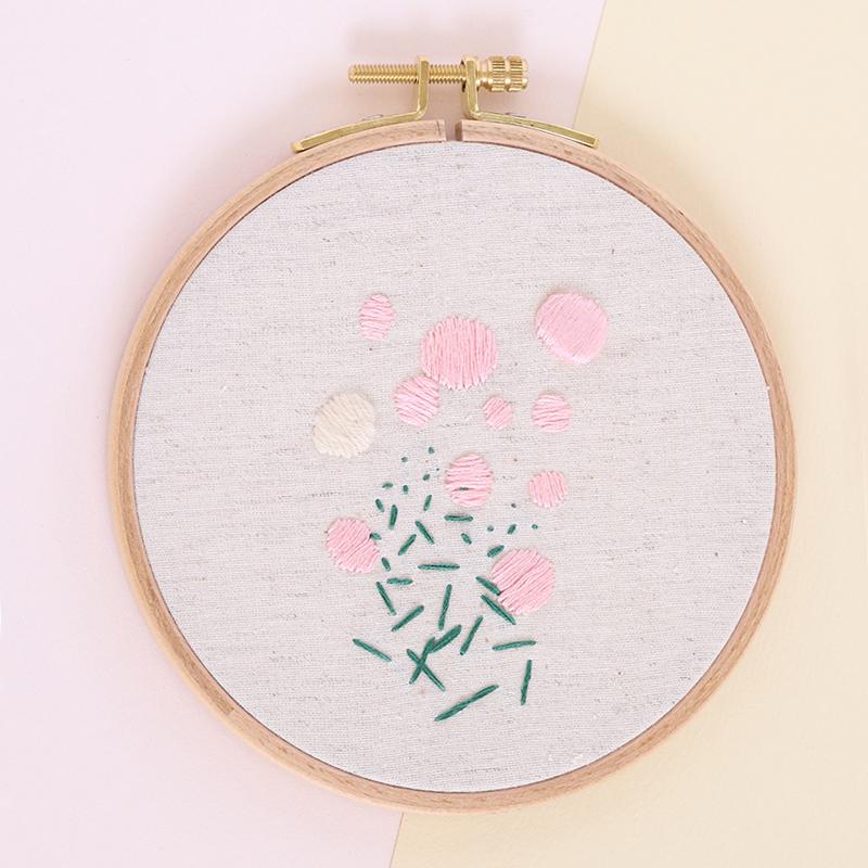 Cadre décoratif Audrey, broderie réalisée à la main, en France, sur du tissu upcyclé. Joli motif abstrait aux tons rose pâle, crème et vert sapin.