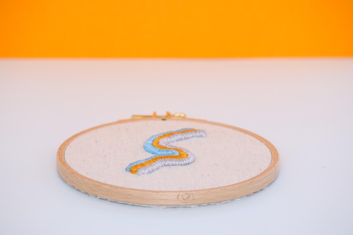 Détail du cadre décoratif Alex, broderie réalisée à la main, en France, sur du tissu upcyclé.
