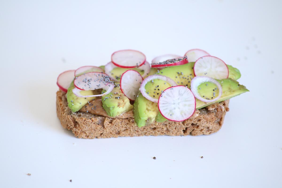 Toast d'avocat au pain et beurres d'oléagineux maison. Agrémenté de radis, d'oignon et de graines.