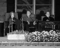 Two residents at a retirement home watch a pleasant autumn day while the third watches the photographer.