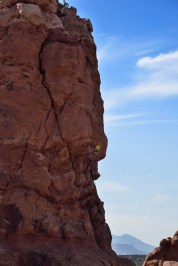 Two climbers begin a descent from one of the rock formations in Arches National Park. One is at the very top, and the other is midway down, in yellow.
