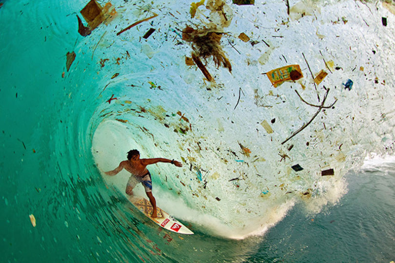 Un surfeur à Java, Indonésie. Il s'agit de l'île concentrant la plus forte population, dont les plages sont couvertes de déchets