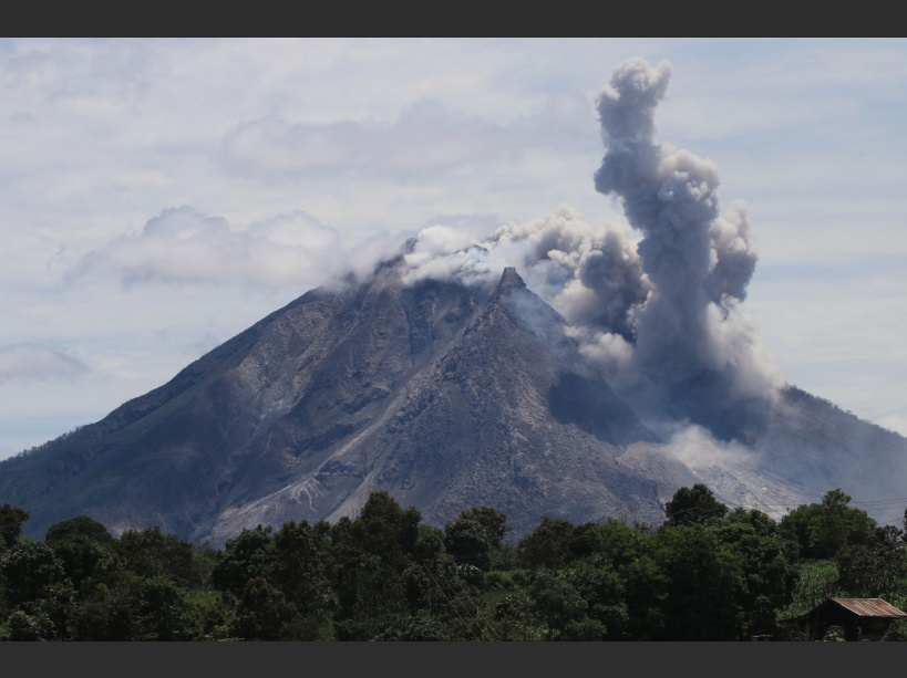The Mount Sinabung volcano spews hot clouds of ash, as seen from the Simpang Empat subdistrict in Karo, North Sumatra on May 22, 2016. The death toll from a volcanic eruption in western Indonesia has climbed to six, an official said on May 22, with fears more could have been trapped by the hot ash. / AFP PHOTO / ARDIANSYAH PUTRA