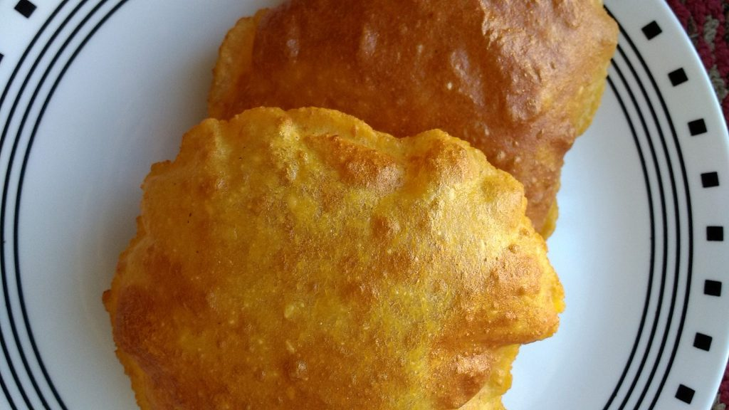 Two piece of aloo poori in a plate.