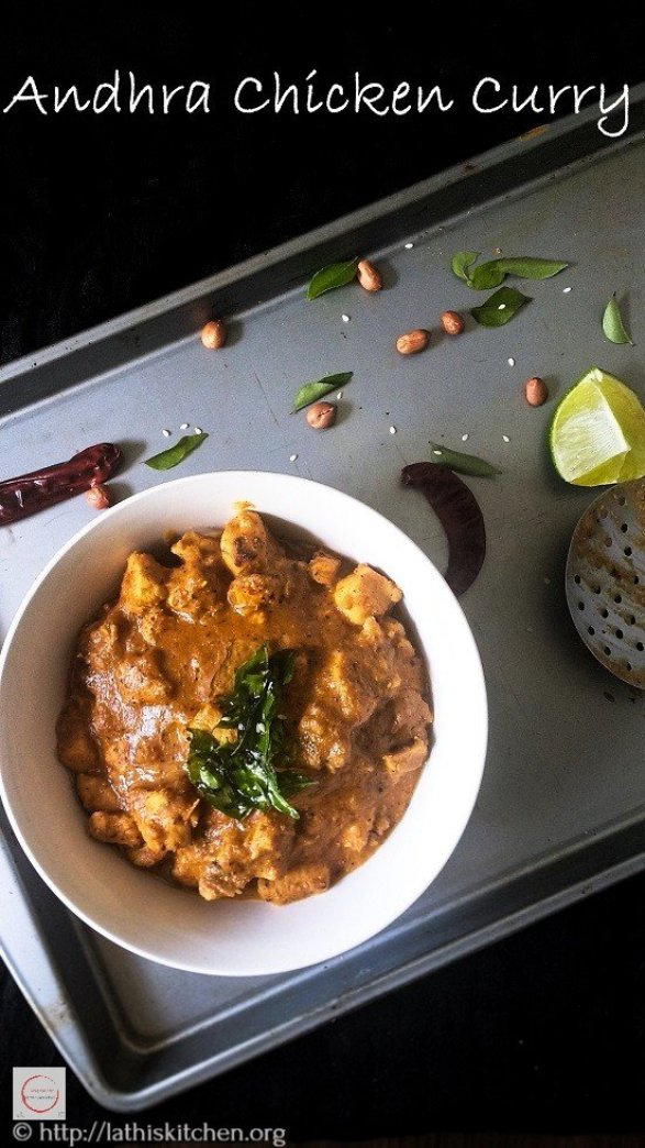 Bowl of Andhra Chicken Curry with peanut, red chilies and lemon wedge on side.