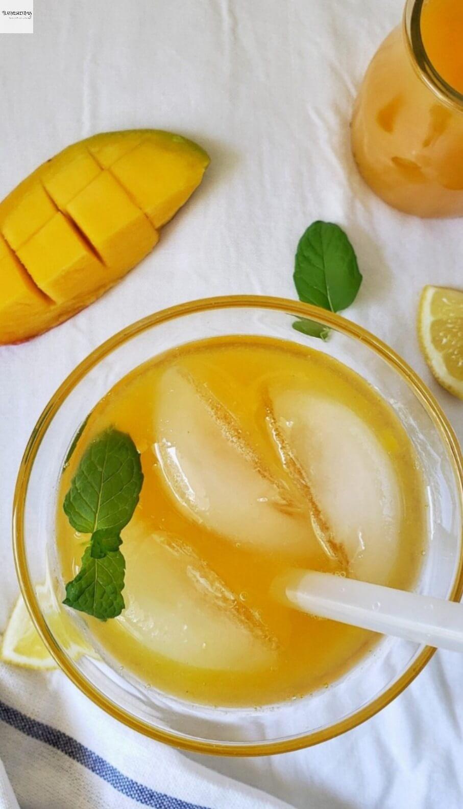 Glass of Mango Lemonade with mango and lemon wedges on side and mint leaves.