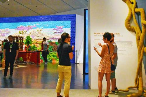 """Guests to the Mi Tierra exhibit discuss the artwork outside Justin Favela's """"Fridalandia"""""""