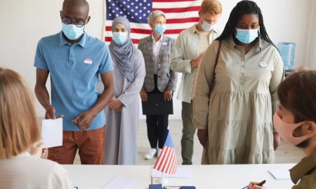 people wearing masks at the polls