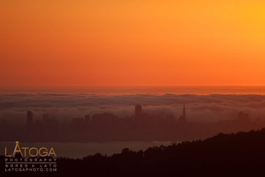 Fog Rolls into San Francisco as seen from a distance at sunset