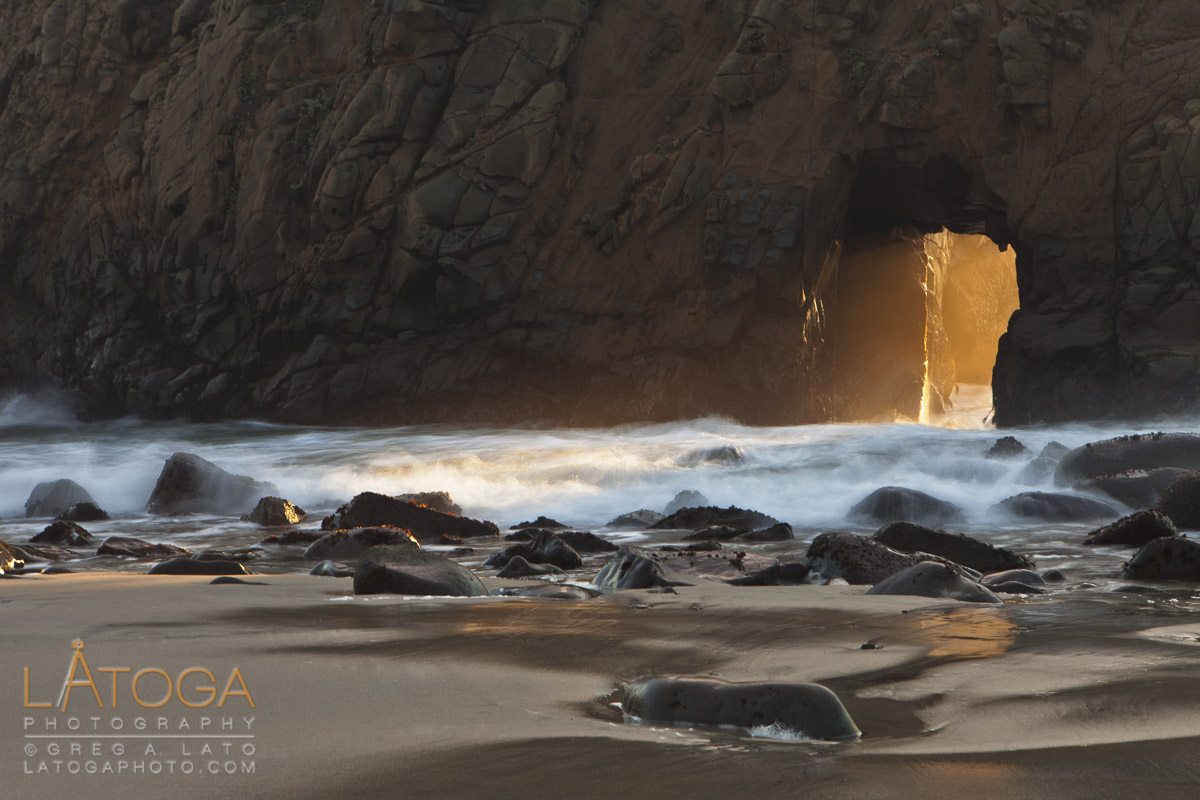 Golden light from sunset creates glowing doorway through sea arch in cliff at Pfeiffer Beach, Big Sur, California.