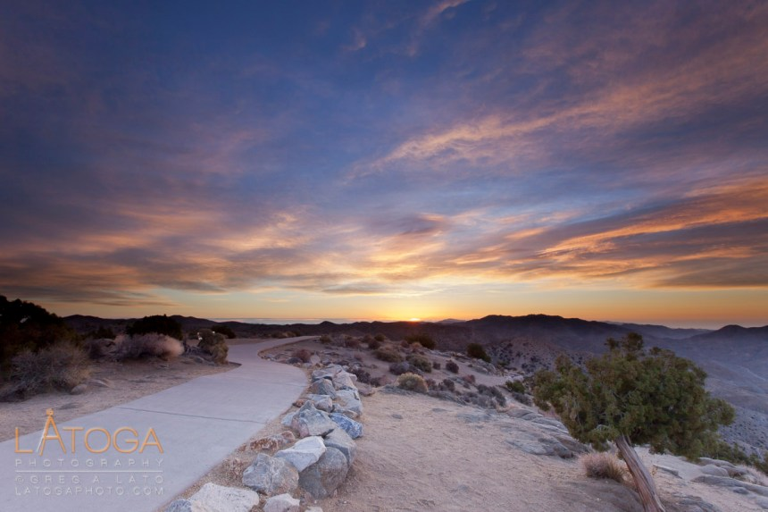 A sidewalk winds off toward the distant rising sun at Keys View, Joshua Tree National Park, California.