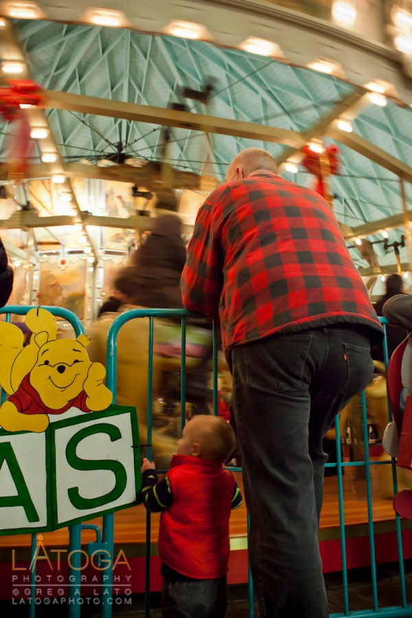 Little boy and adult man standing side by side watching a carousel at Tilden Regional Park in Berkeley, California.