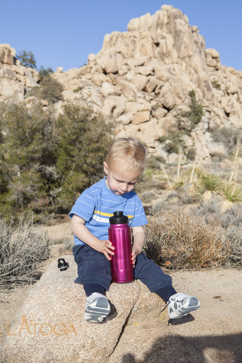 Toddler sits to take drink during hike through Hidden Valley in Joshua Tree National Park, California.