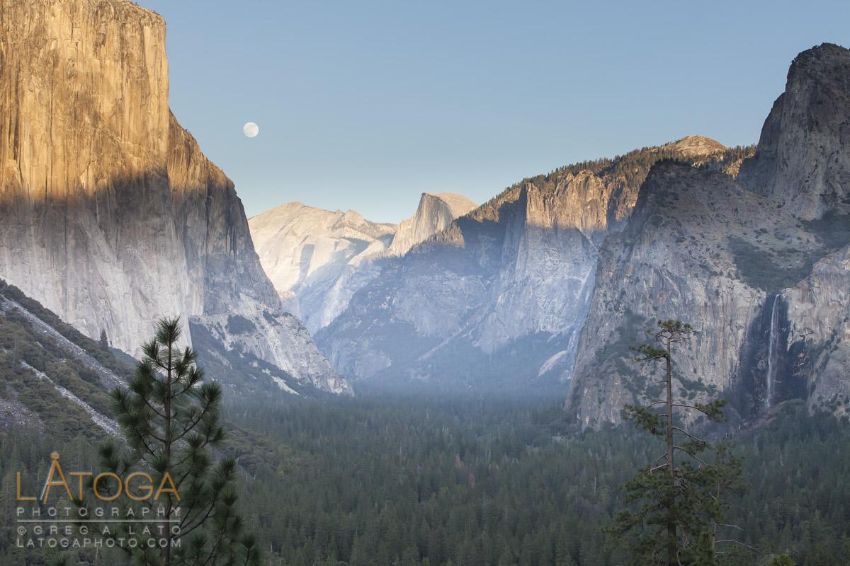 ull Moon rises over Yosemite Valley framed by El Capitan and Bridal Vail Falls in Yosemite National Park, California.