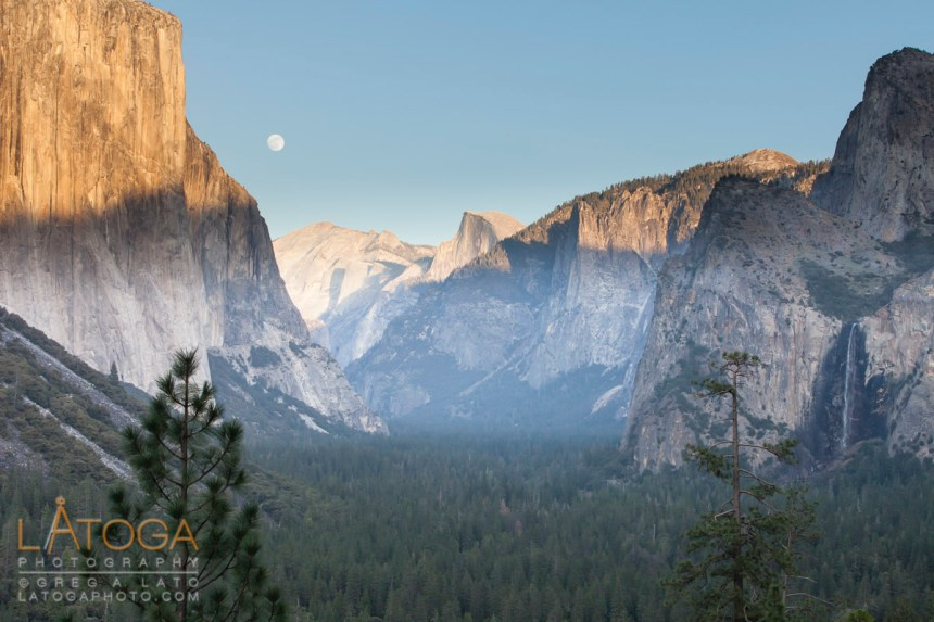 ull Moon rises over Yosemite Valley framed by El Capitan and Bridal Vail Falls in Yosemite National Park, California.